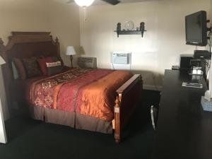 A bed or beds in a room at Longhouse Lodge Motel