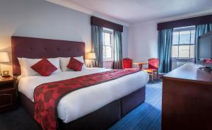 A bed or beds in a room at Belvedere Hotel Parnell Square