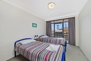 A bed or beds in a room at Akuna 14, 6 Joffre Street,