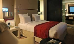A bed or beds in a room at Pullman Lubumbashi Grand Karavia.