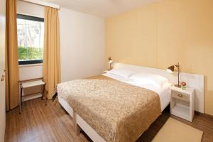 A bed or beds in a room at Apartments Sol Amfora for Plava Laguna