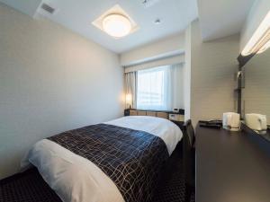 A bed or beds in a room at APA Hotel Higashi-Umeda Minami-morimachi-Ekimae