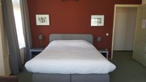 Een bed of bedden in een kamer bij Hotel het Gemeentehuis Uithuizen
