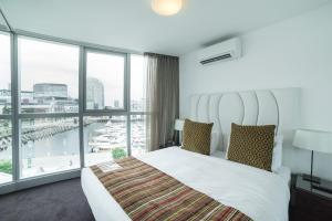 A bed or beds in a room at The Sebel Melbourne Docklands