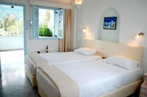 A bed or beds in a room at Drossos Hotel