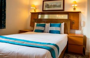 A bed or beds in a room at Aspen Serviced Apartments