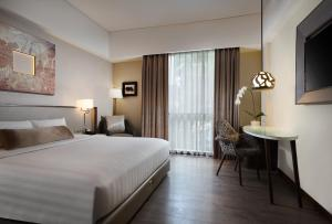 A bed or beds in a room at Mercure Bali Legian