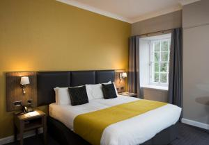 A bed or beds in a room at New Lanark Mill Hotel