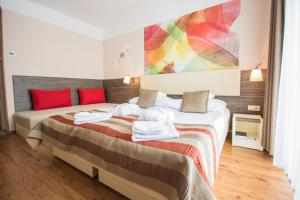 A bed or beds in a room at Harmonia Termal Hotel Sarvar