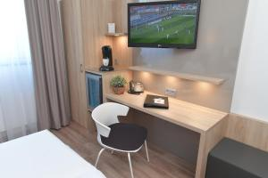 A television and/or entertainment center at Best Western Queens Hotel Pforzheim-Niefern