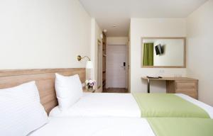 A bed or beds in a room at Repinskaya Hotel