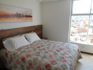 A bed or beds in a room at Apartasuites AV