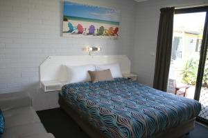 A bed or beds in a room at Ballina Fun`n`Sun Motel