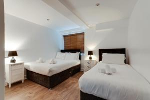 A bed or beds in a room at The Print Works Apartments
