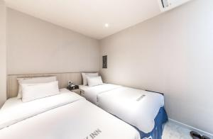 A bed or beds in a room at MyeongDong New Stay Inn