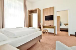 A bed or beds in a room at Villa Auszeit Hotel Garni