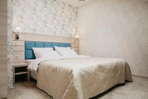 A bed or beds in a room at Boutique Hotel Voskresensky