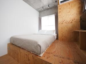 A bed or beds in a room at Smi:re Stay Oshiage