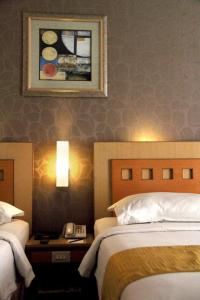 A bed or beds in a room at Serela Riau by KAGUM Hotels
