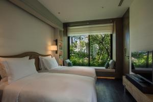 A bed or beds in a room at Rosewood Phuket