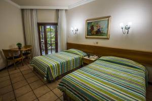 A bed or beds in a room at Catussaba Resort Hotel