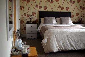 A bed or beds in a room at Orchard Grove B&B