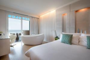 A bed or beds in a room at Savoia Hotel Rimini