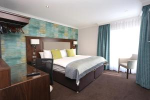 A bed or beds in a room at Best Western Invercarse Hotel