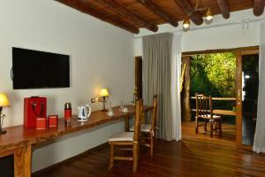 Una televisión o centro de entretenimiento en La Aldea De La Selva Lodge