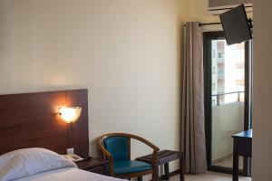 A bed or beds in a room at Hotel Avenida Praia