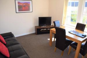 A television and/or entertainment center at Kelpies Serviced Apartments Alexander- 2 Bedrooms