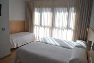A bed or beds in a room at Hostal Universitat
