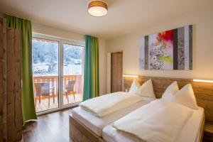 A bed or beds in a room at COOEE alpin Hotel Dachstein