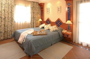 A bed or beds in a room at Pine Cliffs Village & Golf Suites