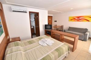 Uma TV ou centro de entretenimento em Mirador Praia Hotel