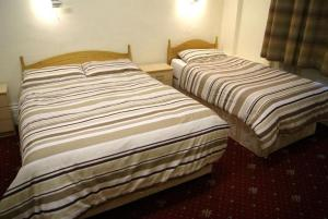 A bed or beds in a room at Stanley House Hotel