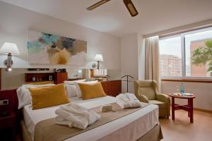 A bed or beds in a room at Senator Barcelona Spa Hotel