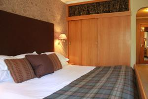 A bed or beds in a room at Roman Camp Country House Hotel
