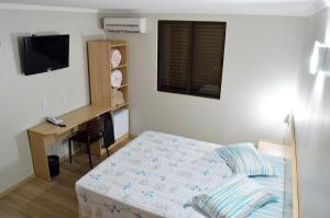 A bed or beds in a room at Hotel Ijuí
