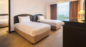 A bed or beds in a room at Bayview Hotel Georgetown Penang