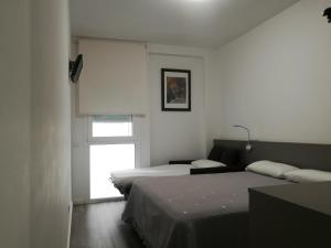 A bed or beds in a room at Hotel Alguer Camp Nou