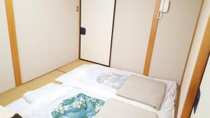 A bed or beds in a room at OYO Manzo Ryokan