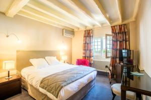 A bed or beds in a room at auberge le relais