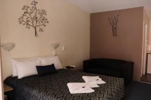 A bed or beds in a room at Bundaberg Spanish Motor Inn