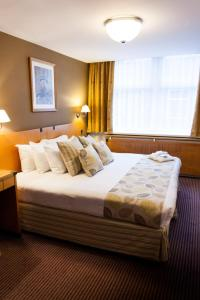 A bed or beds in a room at Best Western Sheffield City Centre Cutlers Hotel