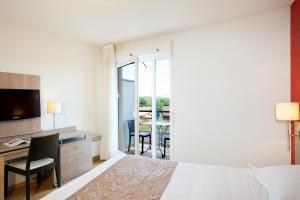 A bed or beds in a room at Séjours & Affaires Genève Gex Les Rives Du Léman