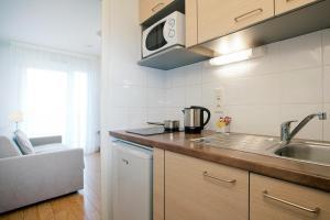 A kitchen or kitchenette at Séjours & Affaires Genève Gex Les Rives Du Léman