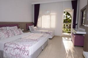 A bed or beds in a room at Lykia Botanika Beach Fun & Club