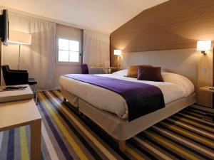 A bed or beds in a room at Mercure Carcassonne Porte De La Cité