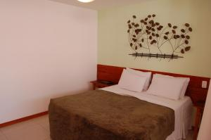 A bed or beds in a room at Palmier Hotel & Convenções
